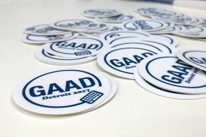 Round white stickers with GAAD Detroit 2017 printed on them, strewn across a white table